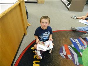 Kolby Hicky, Kindergartner pauses for a picture before getting back to his book.