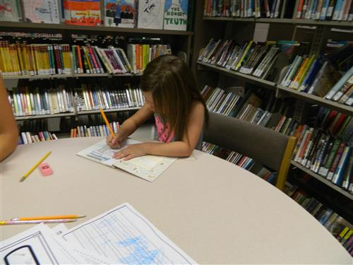 Griffen Grove, Kindergartner is writing her name on the book card before going to the counter to check out.
